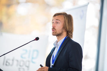 Handsome young man giving a speech at a conference