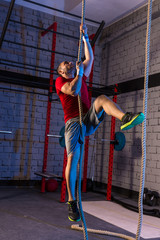 Climb rope exercise man at gym