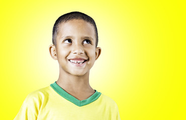 Little Brazilian boy smiling on yellow background