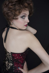 Beautiful red haired young woman wearing lace-up corset