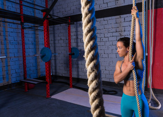 Climb rope exercise woman at gym