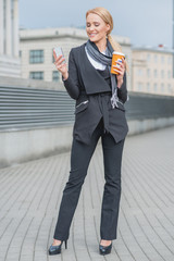 Smiling Businesswoman Holding Phone and Coffee