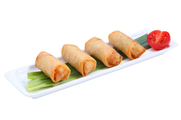 Four Chinese spring rolls on a white long, narrow plate.