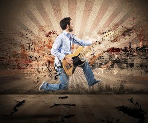 Boy jumping with bass guitar