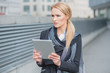 Woman holding a tablet standing thinking