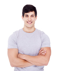 Smiling young casual man looking at camera with arms crossed, is