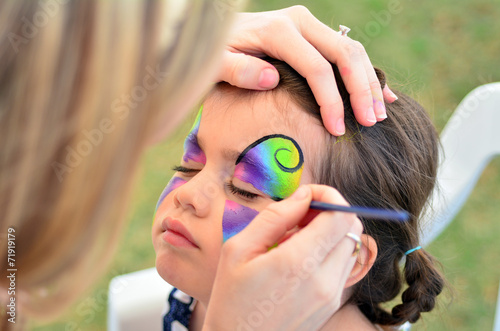 Little girl getting her face painted - 71919179