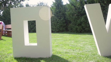 large letters LOVE on the grass on wedding