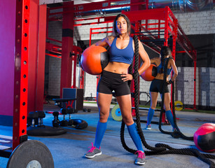 Gym woman with weighted ball and rope
