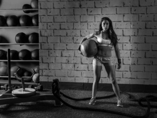 Brunette gym girl holding weighted ball