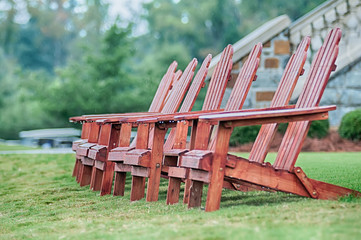 Two wooden adirondack chairs on lush green lawn