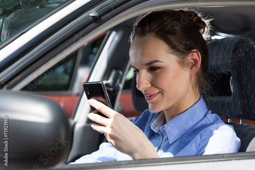canvas print picture Woman texting on mobile phone at car