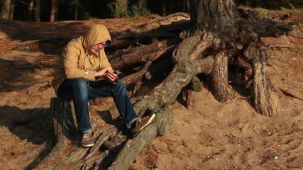 sad man with phone on the beach