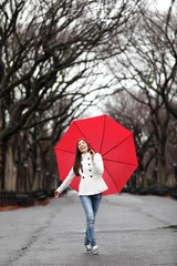 Woman with umbrella in fall in rain