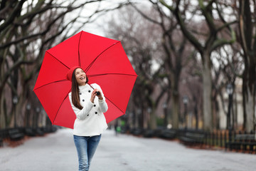 Woman with red umbrella walking in park in fall