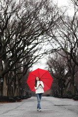 Girl with red umbrella walking in park in fall