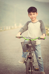 Asian boy riding on his bycicle on the road