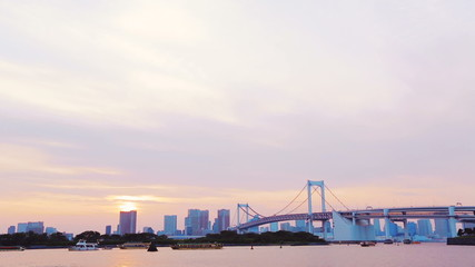 The famous Rainbow Bridge at sunset from Odaiba Bay