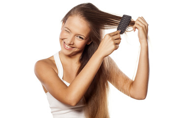 smiling beautiful girl combs her long hair