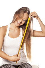 beautiful girl measured her hair with a measuring tape