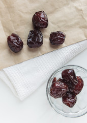 Dried prune in glass bowl and paper bag