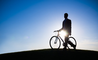 Silhouette of Businessman Holding Bicycle