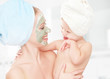 family beauty treatment. mother, baby girl make mask skin