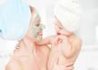 family beauty treatment. mother, baby girl make mask skin