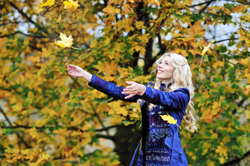 Woman tosses colorful autumn leaves in autumn park