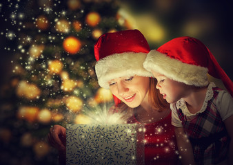 Christmas magic gift and  happy family mother, daughter girl