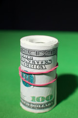 one hundred Dollar roll tightened red rubber band
