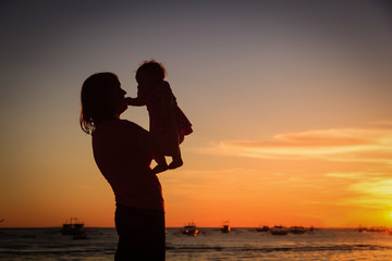 happy mother and baby at sunset beach