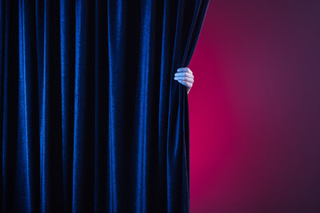 hand opening red curtain. Place for text