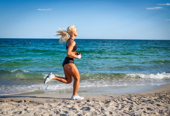Running woman. Female runner jogging during outdoor workout on b