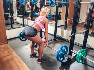 Young sexy woman in the gym doing squat with barbell
