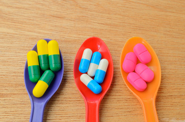 colorful medicine capsule pill on spoon