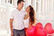 Teenage couple holding red baloons-hearts. valentine day