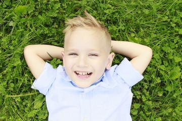 little boy in the meadow smiling