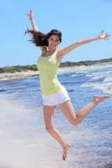 Smiling Pretty Woman in Jump Shot at Beach