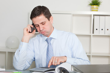 Businessman Calling on Phone While Calculating