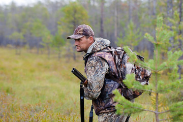 hunter holding a gun and waiting for prey