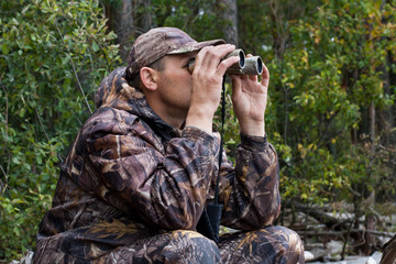 sitting hunter  looks through the binoculars