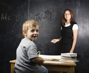 little cute boy with teacher in classroom