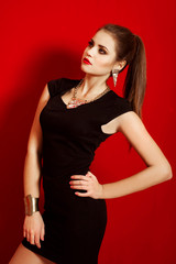 Beautiful girl in a trendy little black dress and jewelry
