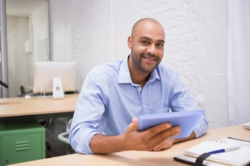 Businessman using digital tablet and diary at desk