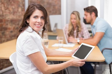 Woman on tablet smiling at camera with colleagues behind
