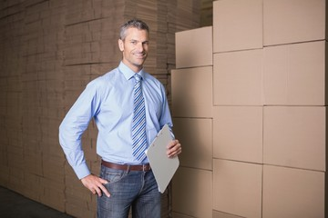Manager holding clipboard against boxes in warehouse