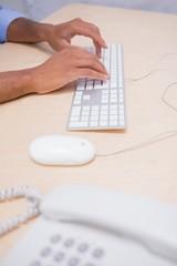 Hands using keyboard at desk