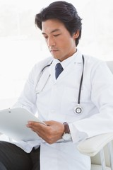 Focused doctor reading over notes