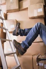 Worker falling off ladder in warehouse